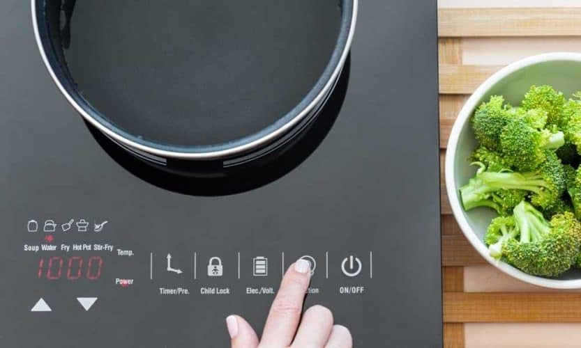 woman pressing control on portable induction cooktop