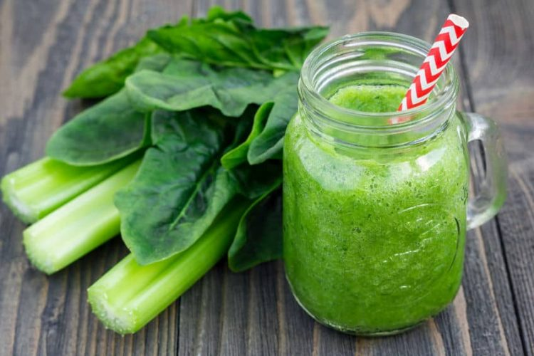 Glass of green juice on wooden table