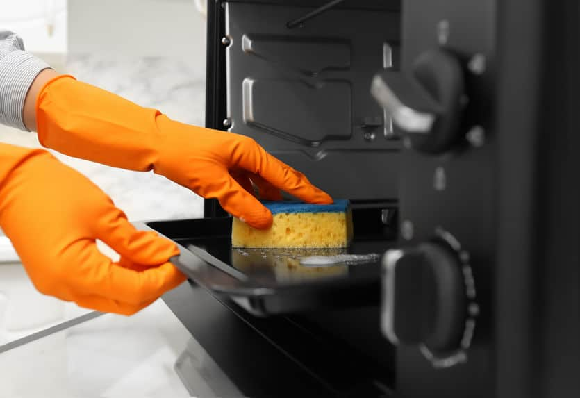 Woman cleaning toaster oven with sponge in kitchen