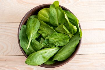 green spinach leaves in ceramic bowl on wooden tabletop