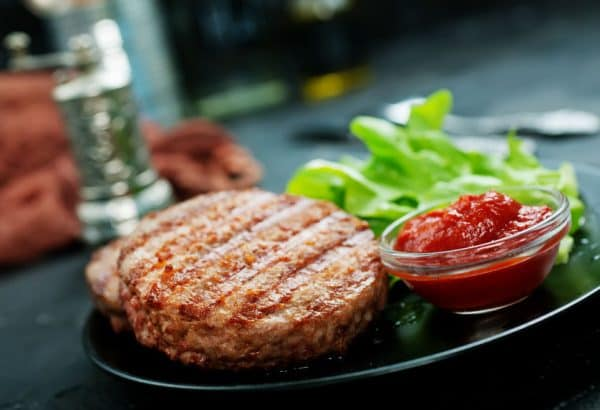 hamburger with lettuce and ketchup on plate on a table