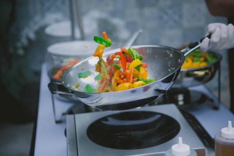 Chef cooking vegetables in wok pan.