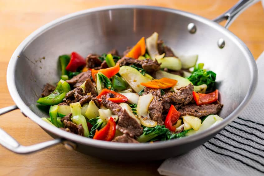 Flank steak beef, peppers, onions and bok choy stir fried in an asian wok.