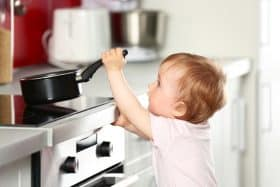 Little child playing with pan and electric stove in the kitchen