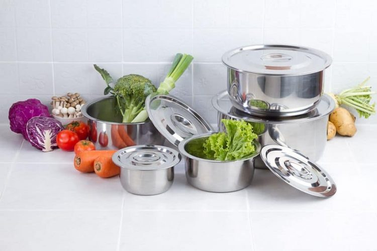 stainless steel cookware set with lids and vegetables