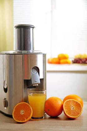 citrus juicer with oranges and fresh orange juice